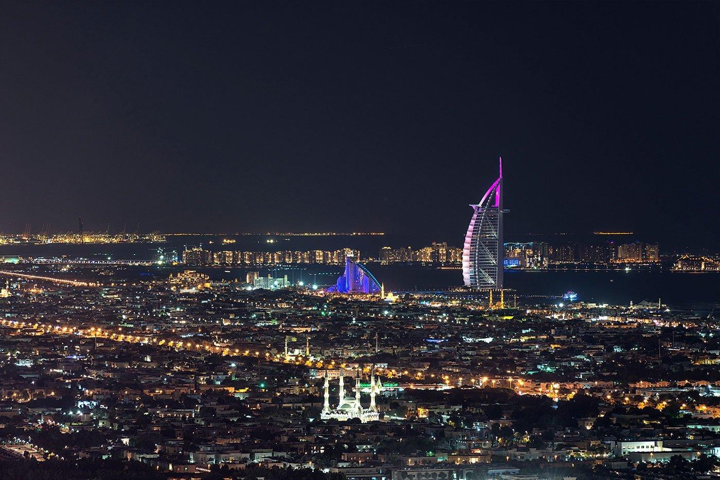 burj al arab at night lit in purple light