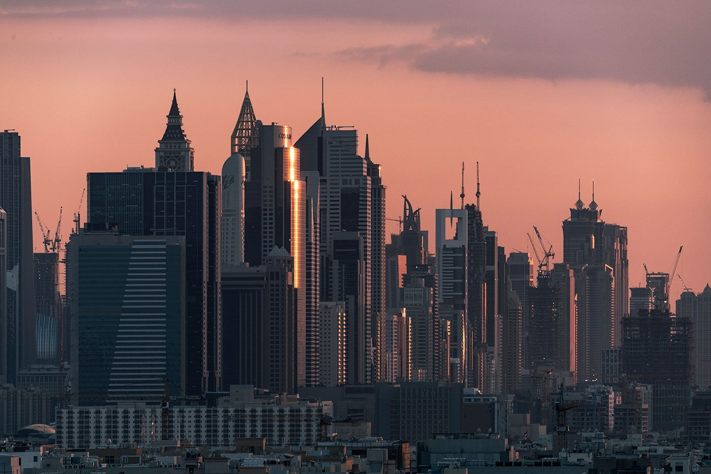 sunset glows reflecting on the glass facades of the Dubai skyline