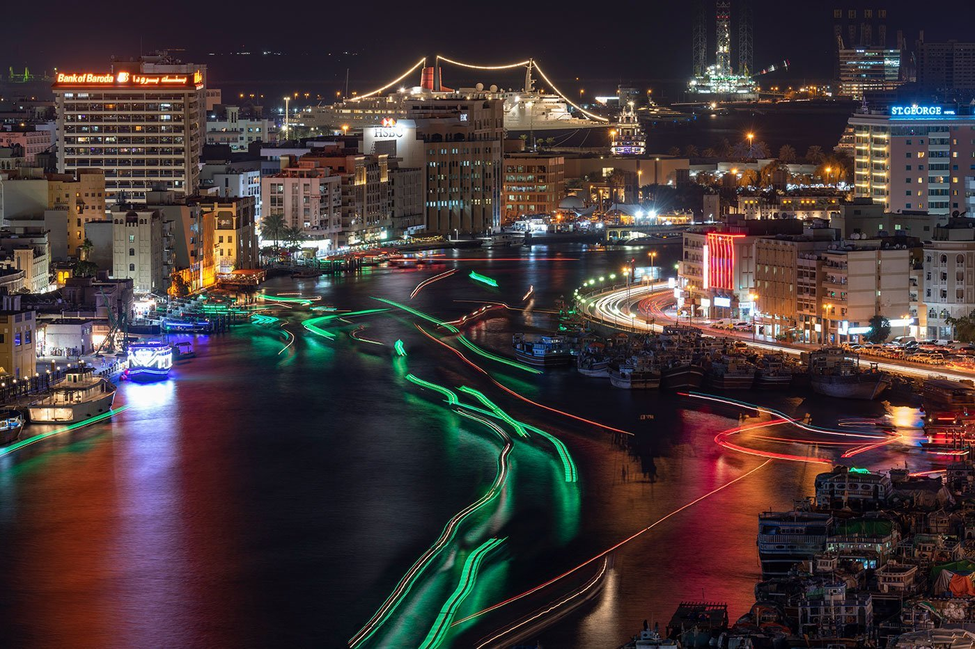 Light trails of boats moving up and down the Dubai creek with the QE2 at the background